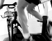 Exercise cycling class, legs pedaling on bike, low angle view