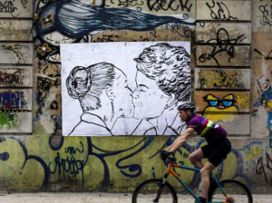 A serigraph made by artist Cela Luz, shows a kiss between presidential candidates Marina Silva (L) of the Brazilian Socialist Party (PSB) and Dilma Rousseff of the Workers' Party (PT) as a man rides his bicycle in Rio de Janeiro September 28, 2014. According to the artist the kiss represents love between people. Brazil's President Dilma Rousseff gained on opposition candidate Marina Silva, increasing her chance to win a hotly contested runoff to the October 5 presidential election, a new poll showed on September 26. The Datafolha survey said Rousseff has 47 percent voter support compared with 43 percent for Silva in a simulation of the expected second-round vote. REUTERS/Ana Carolina Fernandes (BRAZIL - Tags: ELECTIONS POLITICS SOCIETY)