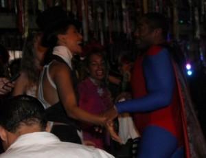 Camila Pitanga de cartola e Lázaro sem camisa, de capa de super-herói. Viu?