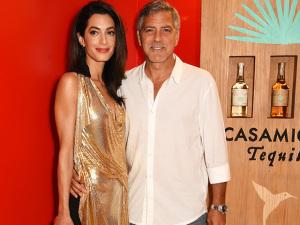 Amal Clooney surpreende e aparece com vestido curto, decotado e dourado