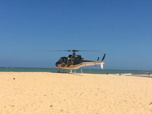 Helicóptero pousando em praia repleta de crianças em Trancoso