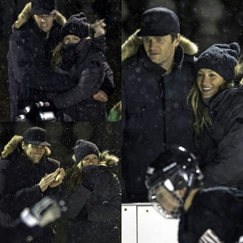 Gisele e Tom agarradas para ver o filho e espantar o frio