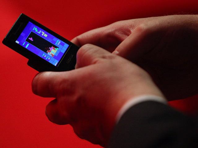 Um delegado joga um jogo de tetris em seu telefone celular  || Créditos: Getty Images