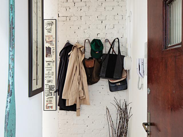 Os tijolos originais das paredes ficaram à mostra, que junto com plantas, dão o tom da decoração