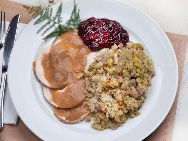 Peito de peru fatiado servido com chutney de cranberry e farofa de castanhas portuguesas: tradição!