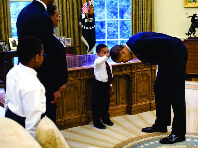 Obama se abaixa após pedido de garoto que queria conferir o cabelo dele || Créditos: Getty Images