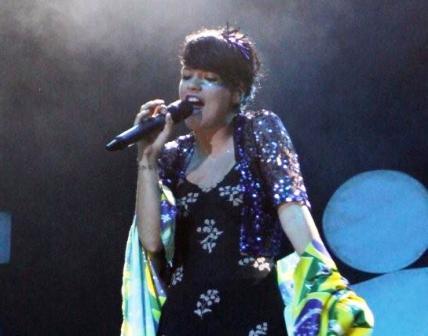 Lily Allen no palco com a bandeira do Brasil: simpatia