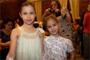 Duas glamuzinhas estão no backstage do Fashion Weekend Kids, no Copacabana Palace, se arrumando para cruzar a passarela com a nova coleção infantil de Ronaldo Fraga